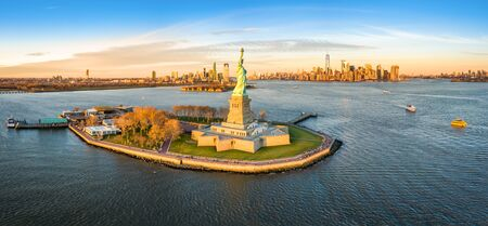 Aerial panorama of the Statue of Liberty in front of Jersey City and New York City skylines at sunset. Stok Fotoğraf