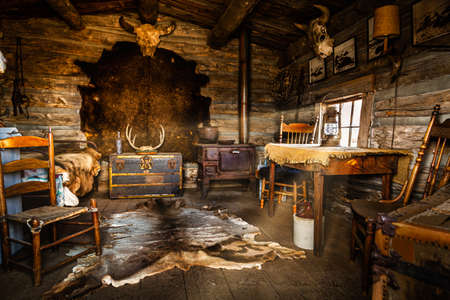 Vintage wild west cabin interior with old chairs, table and other antique objects