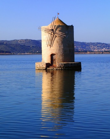 slanted: Old slanted windmill in water, Orbetello, Italy
