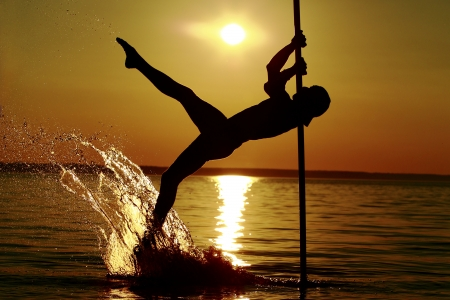 Pole dance boy in the water with a splash photo