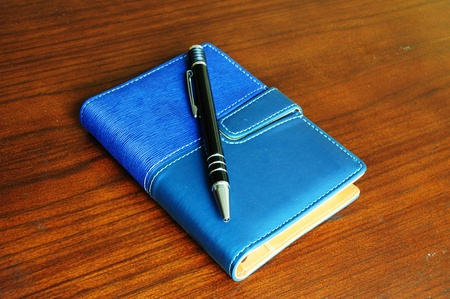 Notebook and pen on wood background photo