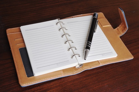 Notebook and pen on wood background Stock Photo - 8794244