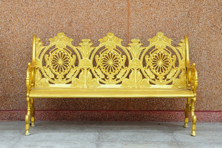 golden iron bench on brown cement wall photo