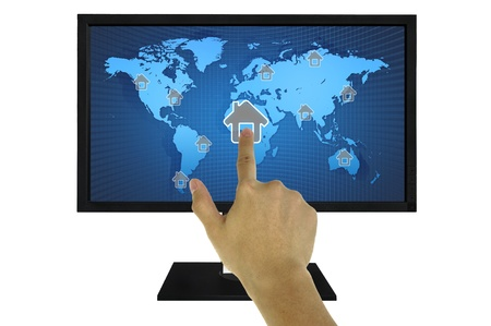 Hand Pressing House Symbol on World Map in Computer LCD Monitor photo