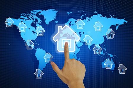 Hand pressing home symbol  on world map