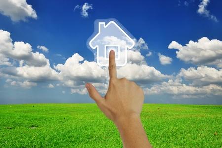 Hand pressing home symbol  on  grassland and blue sky