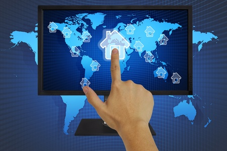 Hand pressing home symbol  on  world map  in computor LCD monitor