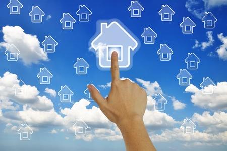 Hand pressing home symbol  on  grassland  blue sky