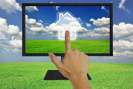 Hand pressing home symbol  on  grassland and blue sky  in computor LCD monitor Stock Photo