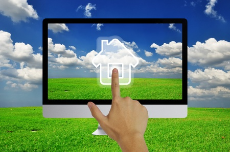 Hand pressing home symbol  on  grassland and blue sky  in computor LCD monitor photo