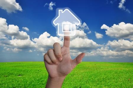 Hand pressing home symbol on glassland Stock Photo - 15219288