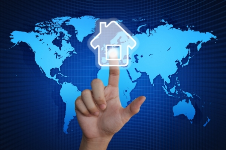 Hand pressing home symbol on world map Stock Photo