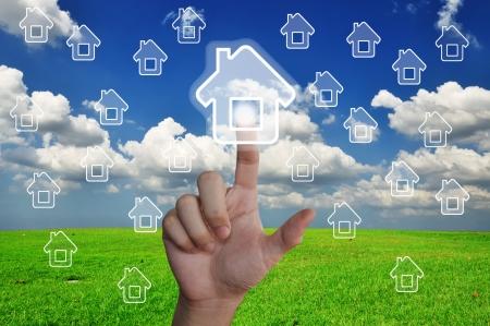 Hand pressing home symbol on glassland Stock Photo