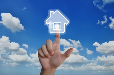 Hand pressing home symbol on blue sky Stock Photo
