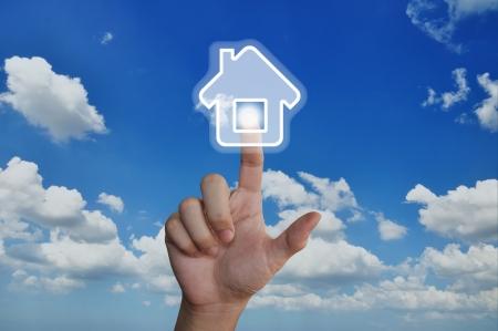 Hand pressing home symbol on blue sky Stock Photo