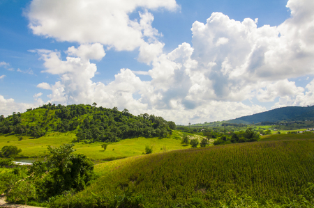 Green field and mountains with cloudy and blue sky. at Flora Park ,Wangnamkeaw - Nakhon Ratchasima , Thailand. Banco de Imagens - 51286899