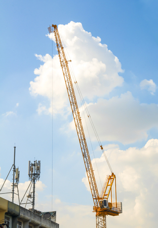 Hoisting crane on blue sky with mobile communication tower on the buildings.