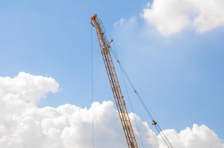 Hoisting crane on blue sky. Banco de Imagens