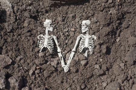 Skeleton couple holding hands together in grave. Love forever concept.