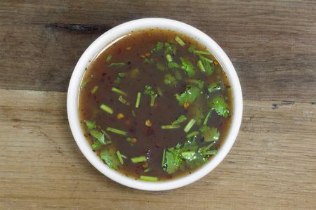 Spicy tamarind sauce on wooden table. Banco de Imagens