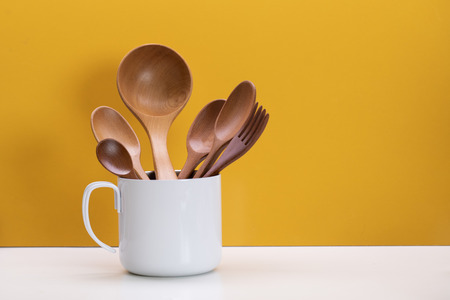 Set of wooden spoons in white cup on yellow background Stock Photo