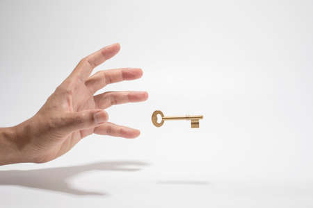 Stretching hand to grab the key, the key to successful concept