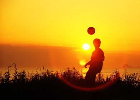 idealism: young soccer players at training at sunset - young footballers training nightly at sunset