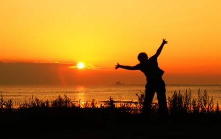 young soccer player jumping at sunset - young footballers training nightly at sunset photo