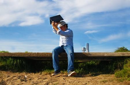 mann: man on bench raises notebook to the floor - mann auf bank wirft notebook auf den boden Stock Photo