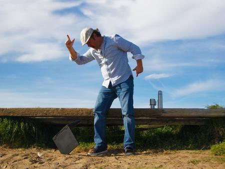 mann: angry man on the beach shouting at his notebook - w�tender mann am strand schimpft auf seinem notebook Stock Photo