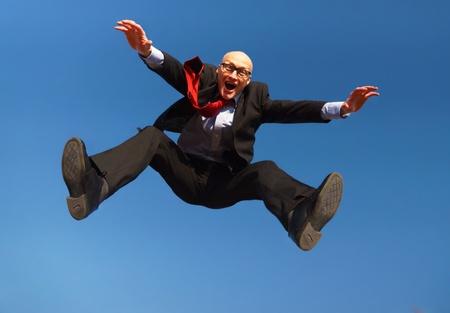 Mann im Anzug mit Brille springt unter einem blauen Himmel