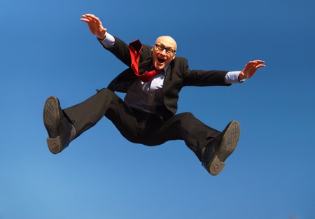 Man in suit with glasses jumping under a blue sky