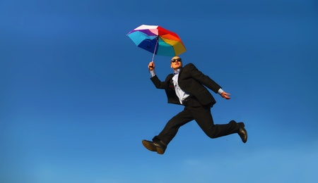 Man in suit with coloured umbrella under a blue sky - Mann in Anzug mit buntem Regenschirm unter blauem Himmel                                photo