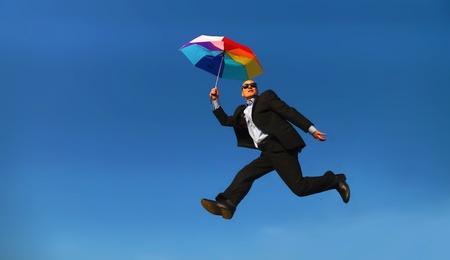 Mann im Anzug mit bunten Regenschirm unter einem blauen Himmel - Mann in Anzug mit buntem Regenschirm Unter blauem Himmel