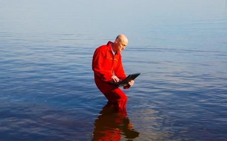 mann: Bald man with sunglasses and red suit with notebook in the sea - Mann mit Glatze, Sonnenbrille und rotem Overall mit Notebook im blauen Wasser
