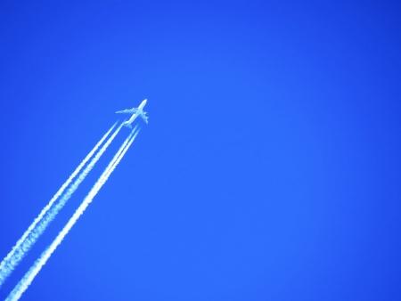 ferien: Flugzeug fliegt in den tiefblauen Himmel hinein - Zeit für Urlaub