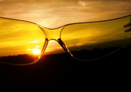 Zeer mooie zonsondergang gezien door geel, sportief zonnebril