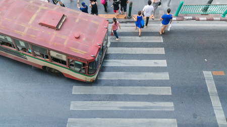 cross street with care: People are walking across road before the bus is going at the crosswalk in top view (aerial photo) Editorial