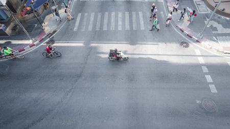 crosswalk: Aerial view of People and bicycle are going across crosswalk and road in city street.