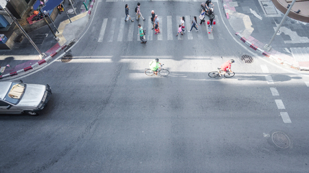 across: Aerial view of People and bicycle are going across crosswalk and road in city street.