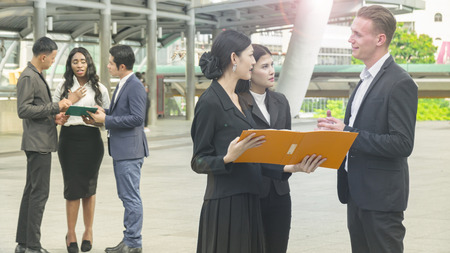 suite: team of business people smart man and woman talk about the project and business work and see on the paper file book in feeling smile and happy with the city space background in the outdoor morning sky