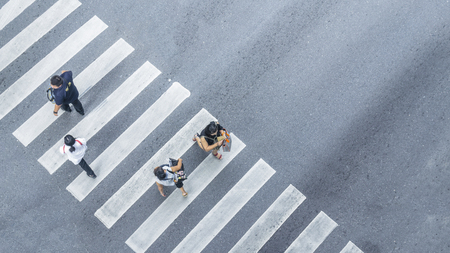 From the top view of people walk on street pedestrian crossroad in the city street with the motorcycle drives pass road ,bird eye view. Archivio Fotografico