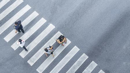 Desde la vista superior de la gente camina en la calle cruce de peatones en la calle de la ciudad con el camino de paso de motos, vista de pájaro.