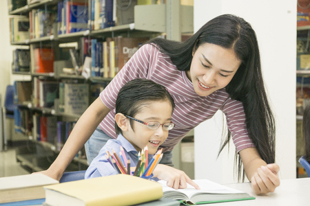 woman teacher and kid student learn with book at bookshelf background