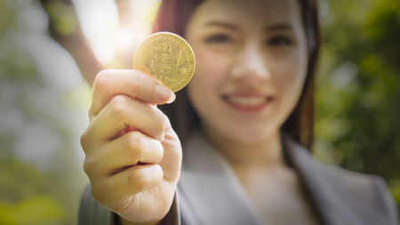 bitcoins - Bitcoin in hand of a casual businesswoman to show the digital currency wondering what the future is.
