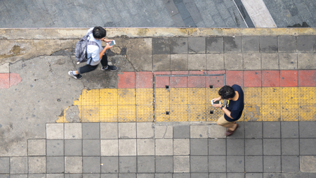Aerial view and top view with blur man with smartphone is walking in business area with pedestrian street and red and yellow block walkway 写真素材