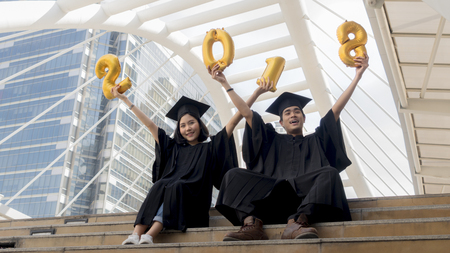 students in graduation suit sit and gold number balloons 2018