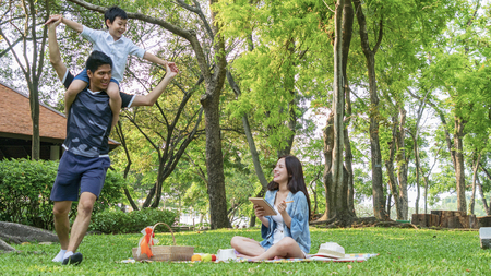 Family Picnic at gaden park Outdoors Togetherness Relaxation Concept with kid rides on the father's neck.