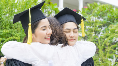 two asian girl students with the graduation gowns and hat hug the parent in congratulation ceremony. Stock Photo