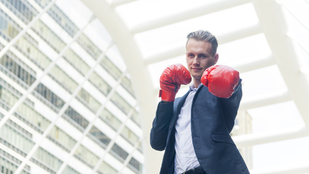businessman with boxing glove hand stand at outdoor Stock Photo